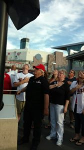 Walt Ihnken, veteran and former CHS employee raises the flag at a Minnesota Twins game while family and friends look on.