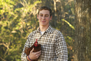 "Trevor Lee, with Rhode Island Red hen, ""Cinderella,"" awarded scholarship for his work in poultry genetics."